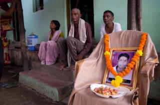 Pravin Soyam's family sit next to a photograph of him