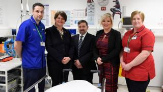 Arlene Foster, Robin Swann and Michelle O'Neill pictured alongside health workers