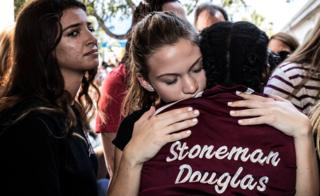 Students from Marjory Stoneman Douglas High School in Parkland, Florida, attend a memorial following a deadly shooting incident, 16 February 2018
