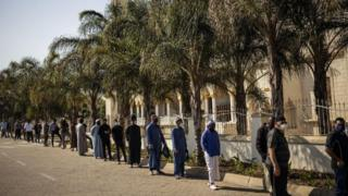 Muslims wearing masks as preventive measure against COVID-19 coronavirus await in line to enter the Nizamiye Mosque ahead of the Friday prayer in Midrand, Johannesburg, on June 5, 2020.