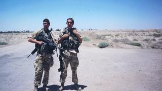 Two men in army uniforms stand holding machine guns in an empty desert/field