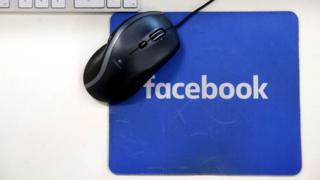 A computer mouse on a Facebook mousemat
