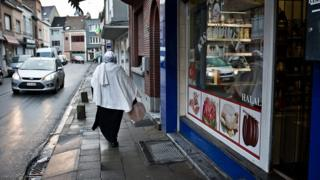A Muslim woman walks past halal shops on January 13, 2014 in Vilvoorde, Belgium