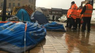Council workers look on to a row of tents