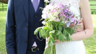 A married couple and wedding bouquet
