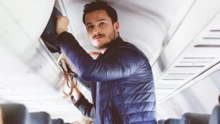 Man puts bag in overhead locker on plane