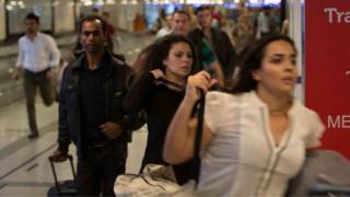 people running around a corner inside an airport, June 28 2016