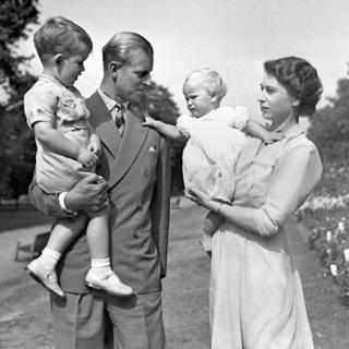 Princess Anne in the arms of Princess Elizabeth with the Duke of Edinburgh, holding Prince Charles, in the grounds of Clarence House, their London residence