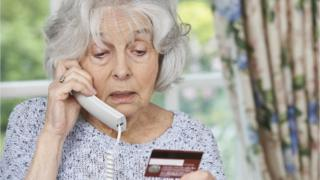 older woman on phone with credit card