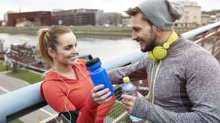Screengrab of man talking to woman who has taken off her headphone