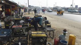 A roadside mechanic repairs electricity generators that are believed to contribute to the pollution