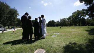 A family gathers in prayer as they visit an Islamic garden in Restland cemetery, Dallas - 17 July 2015
