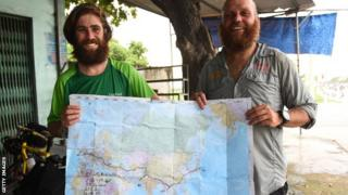 James Owens and Ron Rutland hold up a map of their journey