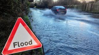 A car driving past a flood sign