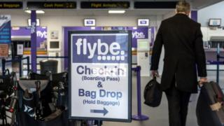 People pass a Flybe airline check-in sign at Exeter Airport on October 18, 2018 in Exeter