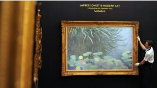 A member of staff poses with a painting entitled Nympheas Avec Reflets de Hautes Herbes by French artist Claude Monet at Sotheby's auction house in central London on 31 January 2013, and due to form part of the Impressionist and Modern Art Evening Sale on 5 February.