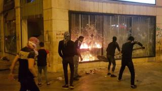 Protesters attack a building in the Lebanese city of Tripoli on 27 April 2020