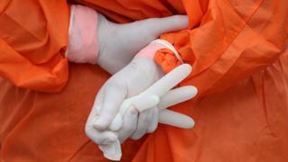 Hospital worker in Chile wears gloves