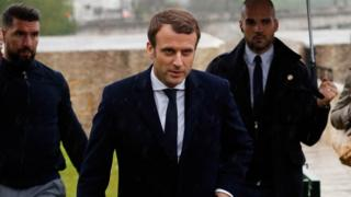 Emanuel Macron, head of the political movement En Marche !, or Onwards !, and candidate for the 2017 presidential election, walks in the rain during a visit to the the Memorial des Martyrs de la Deportation (Deportation Memorial)