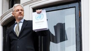 This file photo taken on 5 February 2016 shows WikiLeaks founder Julian Assange addressing the media from the balcony of the Ecuadorian embassy in central London, holding a printed report of the judgement of the UN's Working Group on Arbitrary Detention on his case.