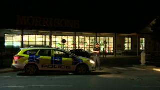 Police officer stands guard next to a police car outside a Norfolk supermarket
