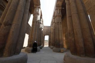 A man sits at the base of a column of Luxor Temple.