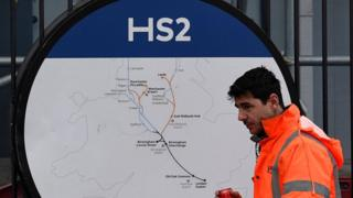 Construction worker in front of HS2 sign