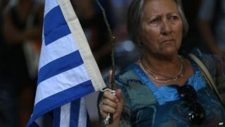 A woman holds a tree branch with a Greek flag tied on it during a rally in support to the Greek government