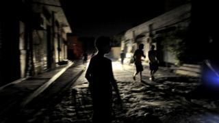 Des enfants circulant dans une rue sombre de Tripoli (archives)
