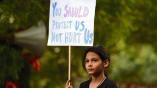 An Indian demonstrator holds a placard during a silent protest 'Not In My Name' in support of rape victims.
