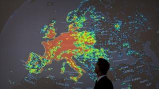Человек стоит у карты с изображением сети зараженных компьютеров