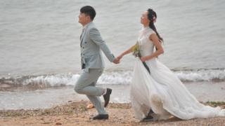 A couple take wedding photos by the sea at the Eight Great Passes (aka Ba Da Guan) on October 12, 2016 in Qingdao, Shandong Province of China