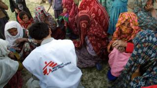 Women sit around an aid worker from Medecins Sans Frontieres waiting for their turn to receive medications a
