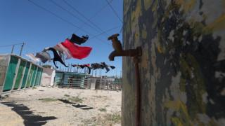 Clothing hangs above a communal tap in Khayelitsha township, near Cape Town, South Africa, 12 December 2017