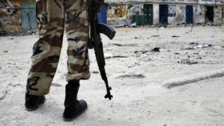 A Somali soldier stands among abandoned houses due to heavy fighting near the Stadium 09 December 2007 in Mogadishu
