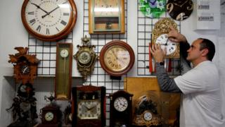 Serge Kertchef, a watchmaker, adjusts the hands on a wall clock in Marseille