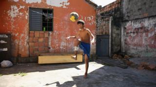 Un adolescente juega fútbol en su casa