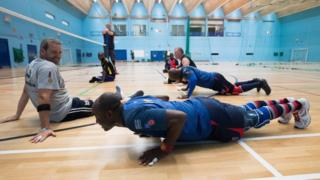 Athletes Daniel Kitcher and Frank Aveh doing press-ups