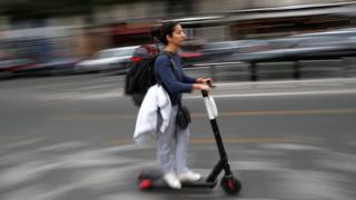 A woman rides an electric scooter without a dock on the street in Paris in September 2019.