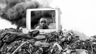 Un hombre mira a través de un marco de un televisor en Mozambique.
