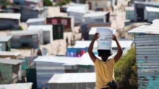 Una mujer llevando un balde de agua a un asentamiento informal en Khayelitsha, cerca de Ciudad del Cabo, Sudáfrica.