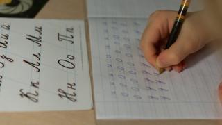 Ребенок переписывает буквы в прописи
