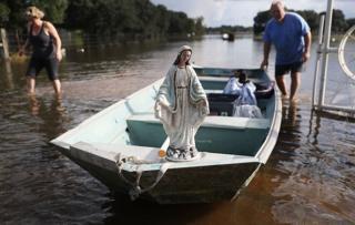 Leigh Babin y su esposo TJ Babin trasladan el barco una estatua de la Virgen María y otros objetos de su casa inundada en Sorrento, Luisiana, EE.UU.
