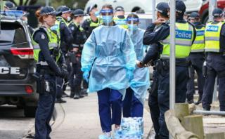 A queue of police guard a path for health care workers to walk through to the housing towers