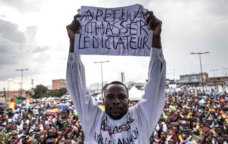 "A man holds a paper with the writing in French ""A call to dismiss the dictator"" in front of a crowd of supporters of the leader of the Cameroonian opposition party Movement for the Rebirth of Cameroon (MRC) during an electoral campaign rally on September 30, 2018"