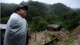 man wrapped in plastic sheeting to protect himself from rain, near destroyed house on muddy hillside, 7 August 2016