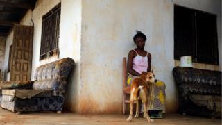 A woman sits with her dog outside her house on the outskirts of Yaounde, Cameroon, 9 October 2018.