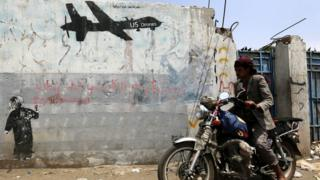 Yemeni rides motorcycle past graffiti protesting against US drone operations in Yemen. 5 September 2016
