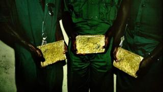 3 men hold gold bar for hand