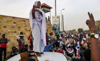 Alaa Salah, a Sudanese woman propelled to internet fame earlier this week after clips went viral of her leading powerful protest chants against President Omar al-Bashir, addresses protesters during a demonstration in front of the military headquarters in the capital Khartoum on 10 April 2019